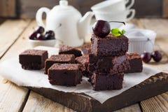 Chocolade brownies met gepoederde suiker en kersen op een donkere houten achtergrond Royalty-vrije Stock Afbeelding