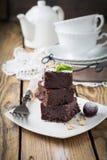 Chocolade brownies met gepoederde suiker en kersen op een donkere houten achtergrond Stock Afbeeldingen
