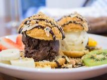 Chocolade choux roomijs met kiwi en aardbei, backgrou wordt geplaatst die Stock Fotografie