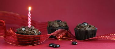 Chocolade cupcake met een brandende kaars en een feestelijk lint, rode achtergrond met exemplaar ruimte, panoramisch formaat royalty-vrije stock fotografie