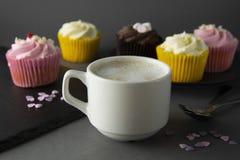 Chocolade cupcakes en koffie, ontbijt met kleurrijke cupcakes Grijze achtergrond Zoet dessert royalty-vrije stock afbeelding