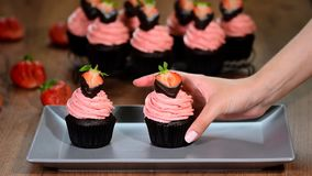 Chocolade cupcakes met aardbei op een houten lijst stock video