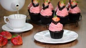 Chocolade cupcakes met aardbeiroom stock videobeelden
