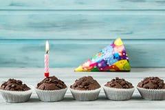 Chocolade cupcakes met kaars op houten lijst tegen blauwe achtergrond en partij GLB Stock Foto
