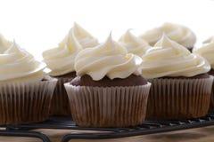 Chocolade cupcakes met vanille die op een witte achtergrond berijpen Royalty-vrije Stock Foto
