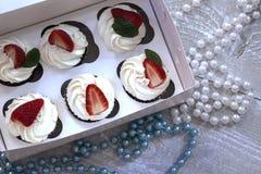 Chocolade cupcakes met witte room en aardbei op bovenkant Stock Foto's