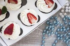 Chocolade cupcakes met witte room en aardbei op bovenkant in Stock Foto