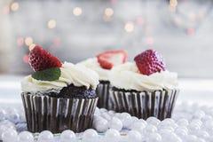 Chocolade cupcakes met witte room en aardbei op bovenkant Royalty-vrije Stock Fotografie