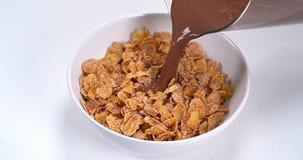 Chocolade die in een kom graangewassen stromen stock footage