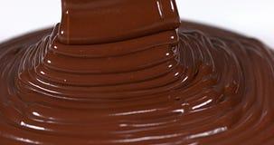 Chocolade die op Witte Achtergrond stromen stock footage