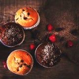 Chocolade donkere muffins op houten achtergrond met gepoederde suiker Royalty-vrije Stock Foto