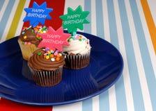 Chocolade drie die cupcakes op een blauwe plaat wordt berijpt met Stock Fotografie