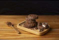Chocolade in een houten houten lepel die van de plaat houten vloer wordt geplaatst stock afbeelding