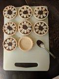 Chocolade en amandeltaartjes op een raad Stock Foto's