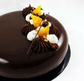 Chocolade en oranje cake met spiegelglans en slagroom stock foto