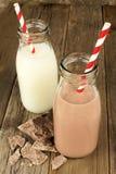 Chocolade en regelmatige melk in flessen op hout Stock Fotografie
