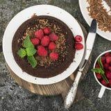 Chocolade gekke pastei met sappige frambozen op een eenvoudige grijze die achtergrond met chocoladeschilfers met munt worden verf Royalty-vrije Stock Afbeeldingen