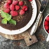 Chocolade gekke pastei met sappige frambozen op een eenvoudige grijze die achtergrond met chocoladeschilfers met munt worden verf Royalty-vrije Stock Afbeelding