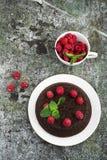 Chocolade gekke pastei met sappige frambozen op een eenvoudige grijze die achtergrond met chocoladeschilfers met munt worden verf Royalty-vrije Stock Foto
