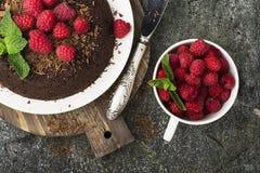 Chocolade gekke pastei met sappige frambozen op een eenvoudige grijze die achtergrond met chocoladeschilfers met munt worden verf Stock Foto's