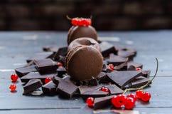 Chocolade kleurrijke macarons over grijs hout met rode aalbessendecor Sluit omhoog Royalty-vrije Stock Fotografie