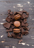 Chocolade macarons meer dan stukken van chocolade op houten uitstekende achtergrond Sluit omhoog Stock Afbeeldingen