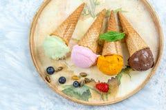 Chocolade, mango, citroen en candyfloss, Roomijs in kegel i een oud dienblad met verse bes, op wit stock foto