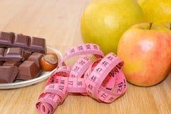 Chocolade met hazelnoten, een meter en vruchten, appelen, bananen, greyfruit Chocolade of fruitdieet royalty-vrije stock fotografie