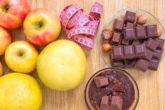 Chocolade met hazelnoten, een meter en vruchten, appelen, bananen, greyfruit Chocolade of fruitdieet royalty-vrije stock afbeeldingen