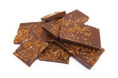 Chocolade met karamel en zoute die stukken op wit wordt geïsoleerd stock foto's