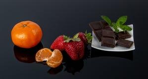 Chocolade met vruchten op darckachtergrond royalty-vrije stock afbeeldingen