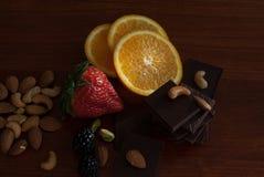 Chocolade, noten, bessen en sinaasappel Stock Fotografie
