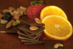Chocolade, noten, bessen en sinaasappel Royalty-vrije Stock Foto's