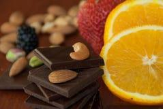Chocolade, noten, bessen en sinaasappel Stock Foto's