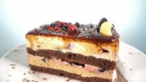 Chocolade scheren die op een plak van fruitcake vallen, het roteren, 4k stock footage