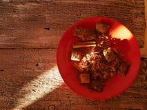 Chocolade, suikergoed, kruiden en cacao op een rode schotel, op een houten lijst royalty-vrije stock foto's
