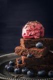 Chocoladebrownie met bosbes en roomijs op de uitstekende plaatverticaal Royalty-vrije Stock Afbeelding
