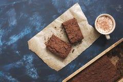 Chocoladecake, koffie met heemst met cacaopoeder wordt bestrooid, blauwe abstracte achtergrond die Royalty-vrije Stock Foto's