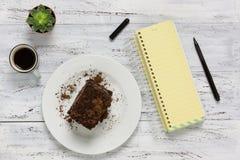 Chocoladecake, leeg geel notitieboekje, koffie, vork en pen op w Stock Foto's