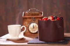 Chocoladecake met aardbeien en kersen die op een houten lijst liggen Stock Afbeelding