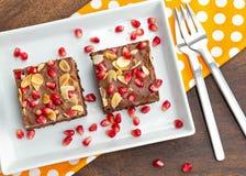 Chocoladecake met granaatappel en amandel wordt verfraaid die Stock Afbeelding