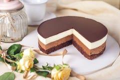Chocoladecake van drie verschillende lagen, het wit, de melk en dark van de chocolademousse met chocolade wordt gemaakt die Stock Foto's