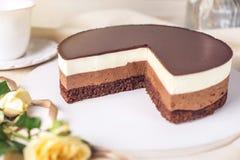 Chocoladecake van drie verschillende lagen, het wit, de melk en dark van de chocolademousse met chocolade wordt gemaakt die Stock Afbeeldingen