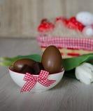 Chocoladeeieren in kom op houten lijst Paaseieren in Mand Stock Afbeeldingen