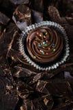 Chocoladefondantje op chocoladeachtergrond Stock Afbeeldingen