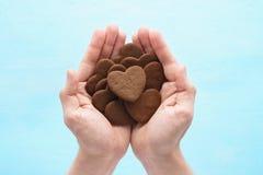 Chocoladehart gevormde koekjes in mensenhanden Achtergrond voor een uitnodigingskaart of een gelukwens royalty-vrije stock fotografie