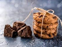 Chocoladekoekjes, die met een kabel worden gestapeld en worden gebonden, stukken van zwarte chocolade, op een geweven achtergrond royalty-vrije stock fotografie