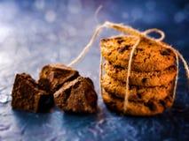 Chocoladekoekjes, die met een kabel worden gestapeld en worden gebonden, stukken van zwarte chocolade, op een geweven achtergrond stock afbeelding