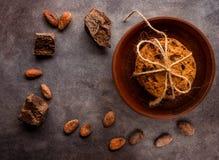 Chocoladekoekjes, met een kabel worden gestapeld en worden gebonden, stukken van zwarte chocolade, en verspreide cacaobonen op ee stock foto's