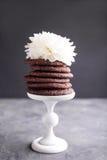 Chocoladekoekjes op een wit die voetstuk met witte bloem wordt verfraaid Royalty-vrije Stock Foto's